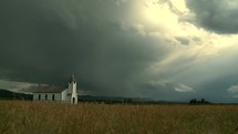 Grass blowing in the wind in a field with a country church under a stormy sky.