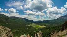 Timelapse of clouds and shadows over a valley between two mountain ranges.