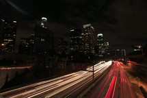 lights from moving cars on a highway in a city at night