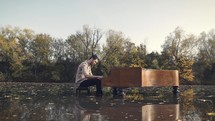 a man playing a piano in water