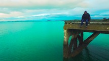 a man sitting at the end of a pier