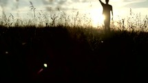 Silhouette of a man walking through a field at sunrise, giving thanks and praising God.