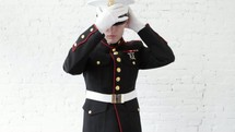A young Marine putting on his hat, adjusting his collar, and slowly saluting