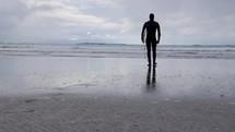 surfer walking on a beach