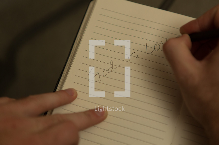 """Man writing """"God is love"""" in notebook"""
