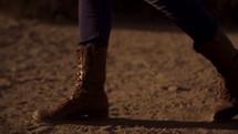 Boots walking through dirt in the desert.
