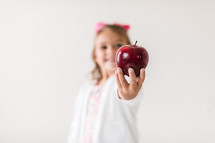 student holding an apple