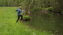 Teen jumping into the river water.