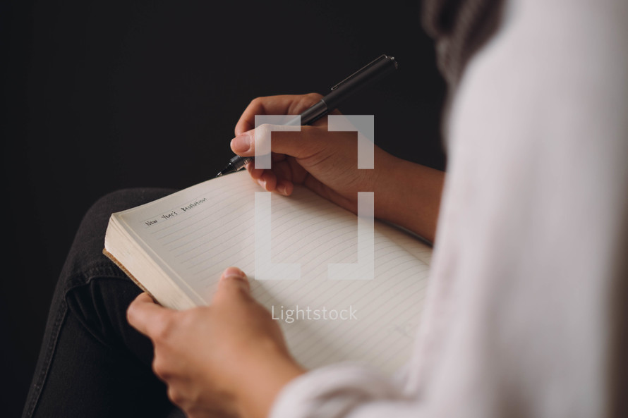 New Year's Resolutions being written in a journal.
