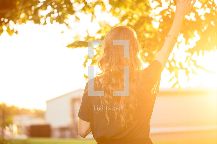 woman with her hand raised in worship standing outdoors under intense sunlight