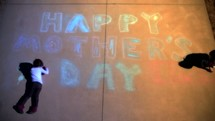 Video with 7 shots of a young girls making a Mother's Day message in chalk on a driveway.