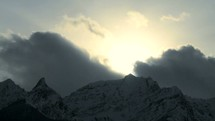 Timelapse of clouds over a snow covered mountain.
