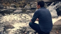 Man sitting outside by a waterfall appreciating the beauty of nature.