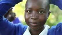smiling girl balancing a water jug on her head in Kenya