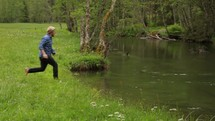 Slow motion shot of a teen boy jumping into the river water.