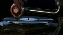 placing a needle on an antique phonographe record player