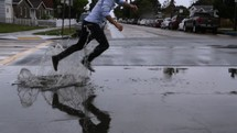 man jumping in a puddle on a rainy day