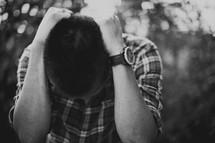 A man, head bowed, seeking out God in prayer