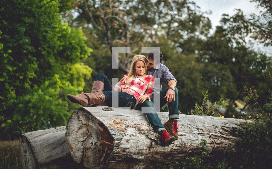 man and woman resting on a fallen tree trunk