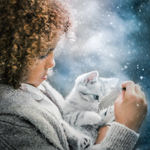 a child holding a kitten in the snow