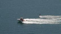 Jet boat pulling a water skier across a lake.