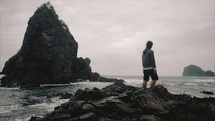 a man standing on a rocky shore watching the ocean