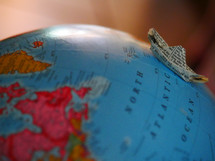 paper boat on the Atlantic Ocean on a globe