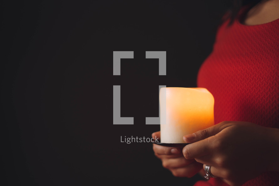 A woman holds a brightly burning candle.