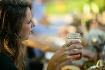 a woman drinking out of a mason jar glass