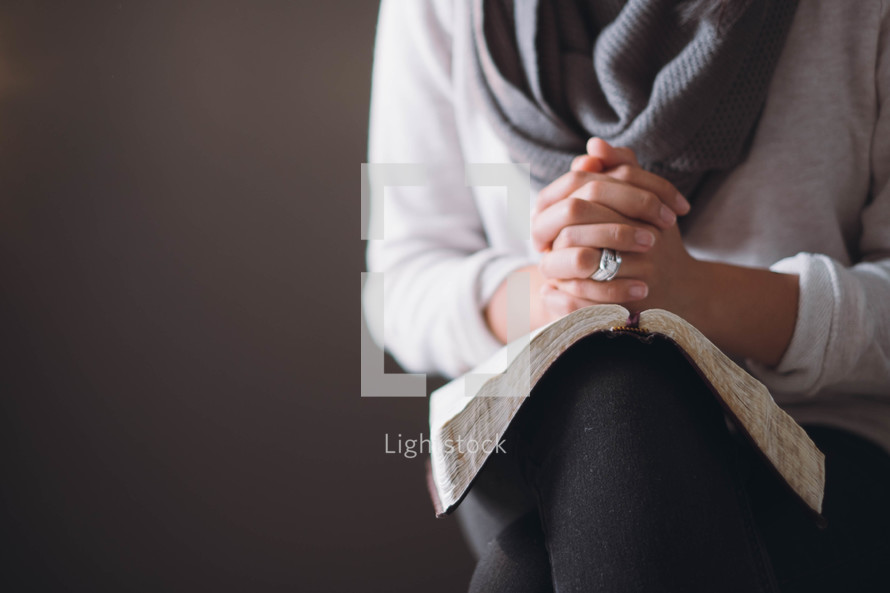 A woman sits with hands clasped on an open Bible.