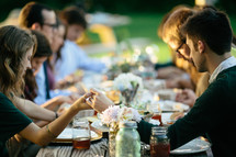 family holding hands in prayer at a dinner table
