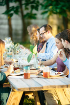 family eating dinner at a dinner table outdoors