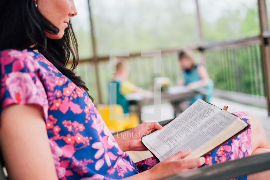 a mother reading a Bible while her children color on a porch