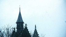 snow falling on church steeples