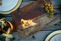 slice of pie and grapes on a wood plater