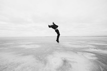 a man leaping in the air over the great salt plains in Oklahoma