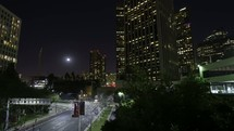 Timelapse of city downtown at night with building and skyscraper lights and traffic in a tunnel.  This time-lapse was filmed in Los Angles, California.