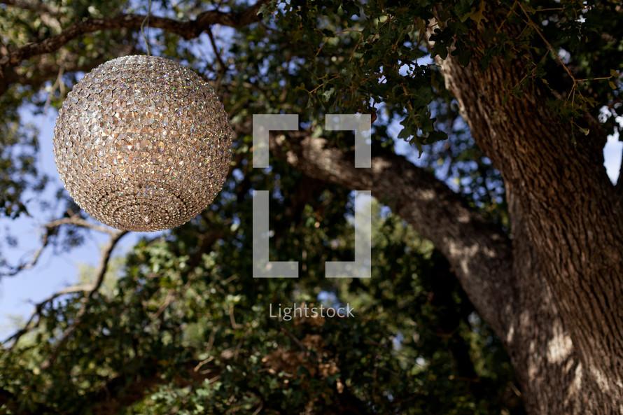 Jeweled globe hanging in a tree