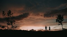 Silhouette of a couple walking on top of a hill during sunset