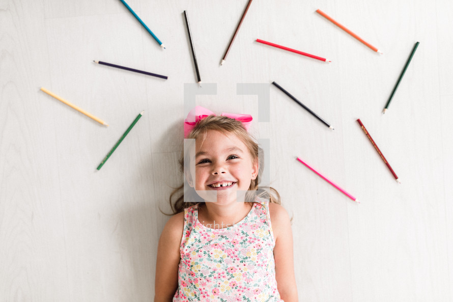 kid surrounded by colored pencils