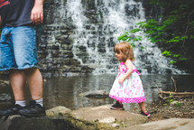a father and daughter hiking near a creek and waterfall