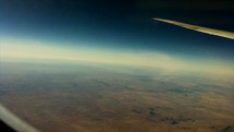 Timelapse of earth below as seen from an airplane window.