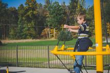 a boy child on playground equipment