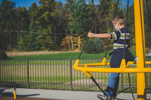 a toddler boy on playground equipment
