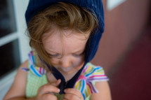 a toddler girl fastening a winter hat in summer
