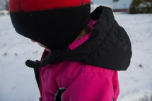 a little girl in a snowsuit and winter coat