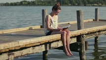 woman reading a Bible sitting on a dock