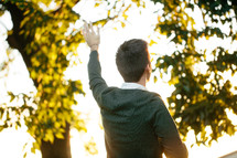 Back of a man standing outside with his arm raised in praise.