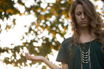 a young woman with hands in worship outdoors