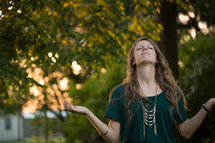 a woman with head tilted up to God standing outdoors